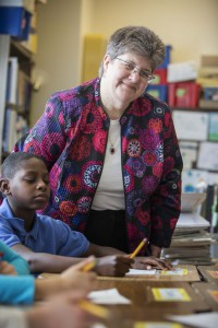 Photo of principal Bernal in a classroom next to a student's desk