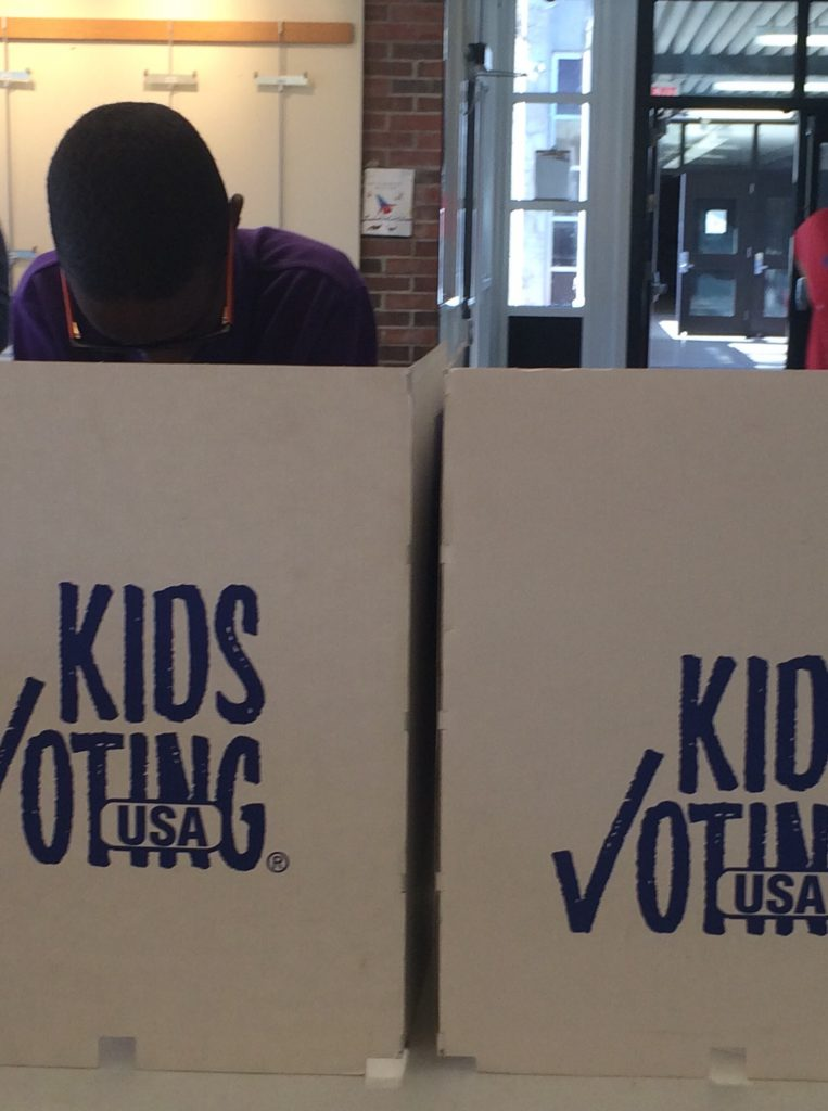 A seventh-grade voter filled out his ballot inside a Kids Voting booth.