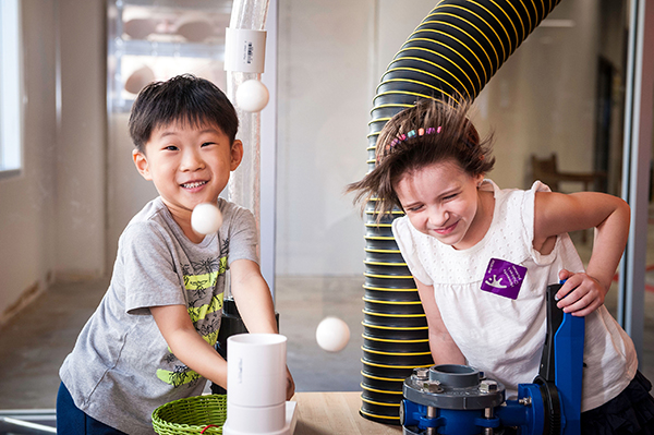 Photo: Two children play with air launchers at the Minnesota Children's Museum