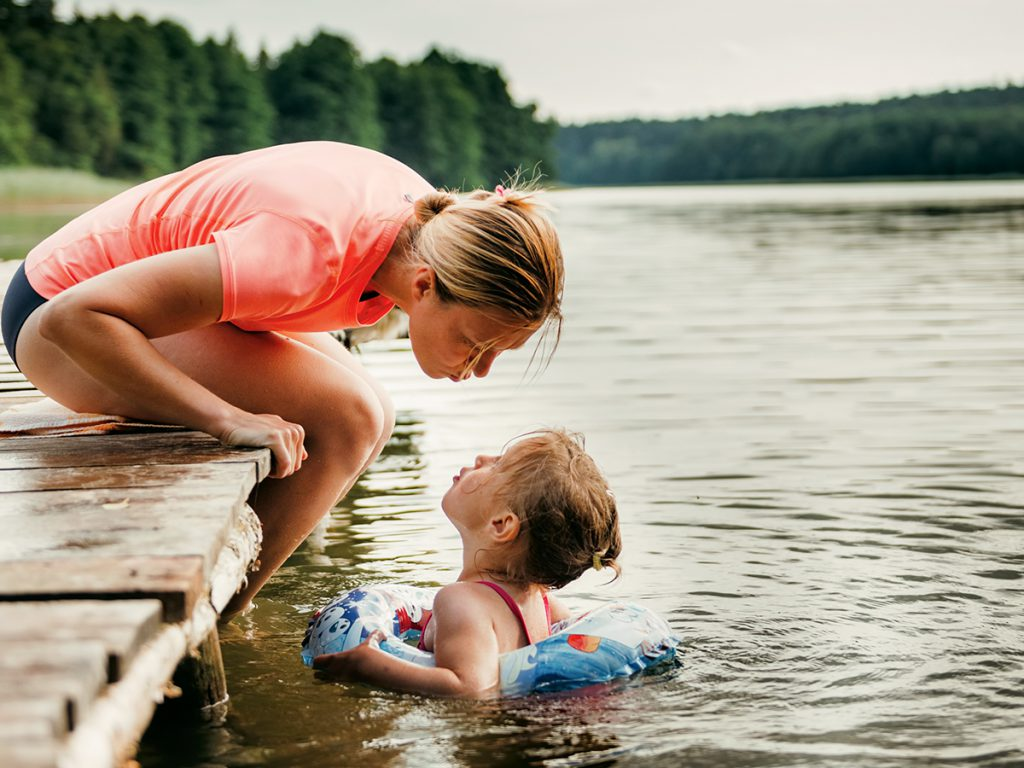 A mother leans over a pier as her daughter swims with an innertube in a lake.