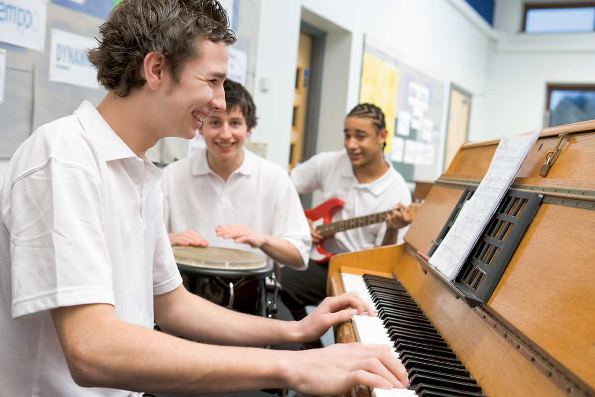 In a music classroom, one student plays piano, while one plays a drum and another plays guitar