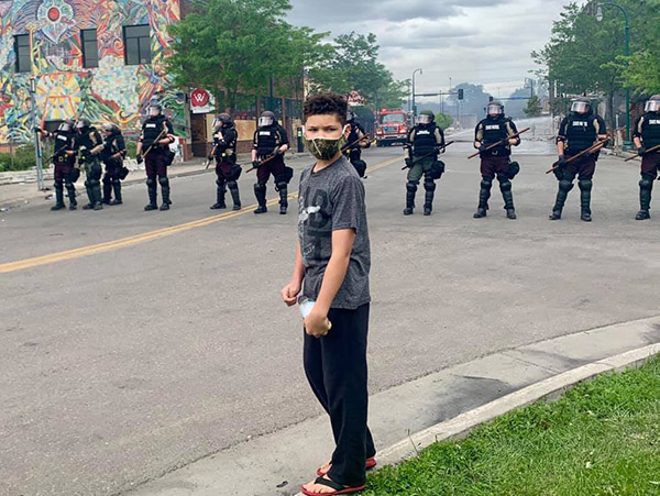 Young man wearing a mask and standing in front of a line of riot police