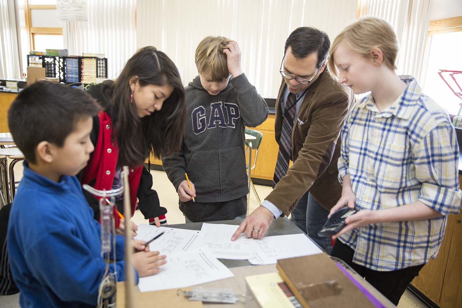 A science classroom experiment with four students and a teacher looking a written data.