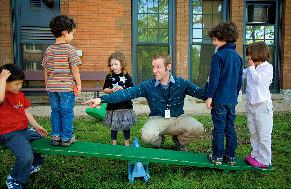 Children play on a teeter-totter at the S. G. Moore Lab School