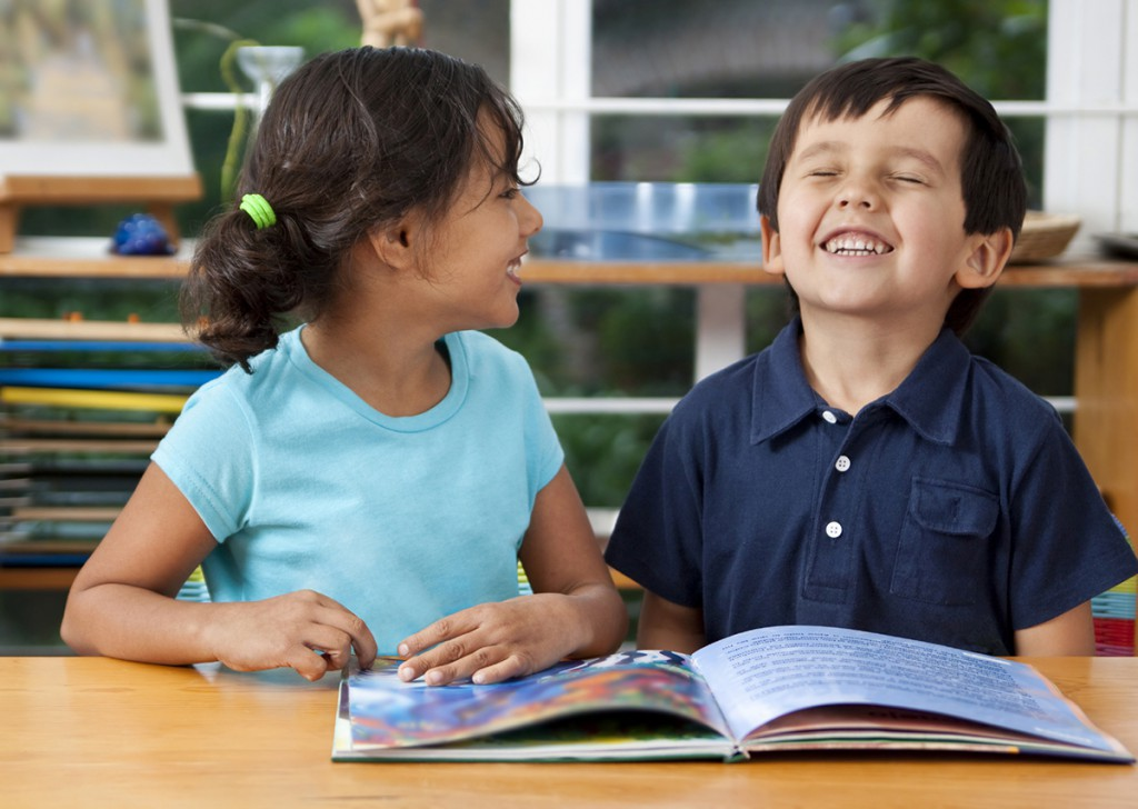 Two young students reading and smiling