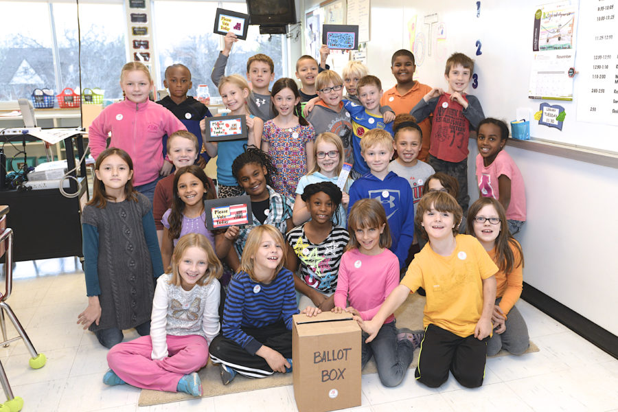 """A classroom of students posing with a """"ballot box"""""""