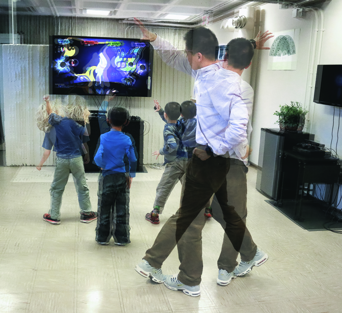 Three children and Zan Gao copy movements on a video screen