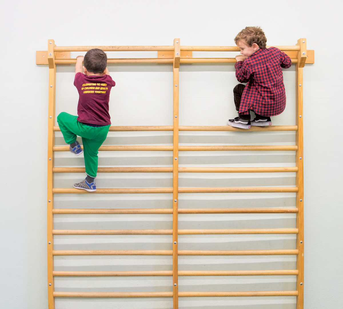 Preschool boys climbing on ladder