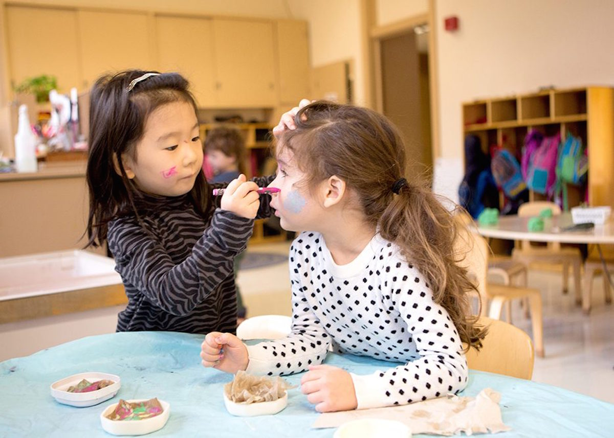 Photo: A preschool girl paints her classmate's face at a classroom table.