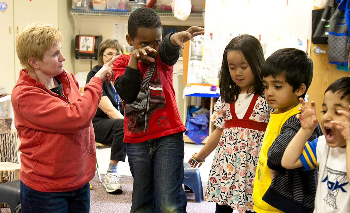 Photo: Students practice their roles with support from an Early Bridges classroom teacher.