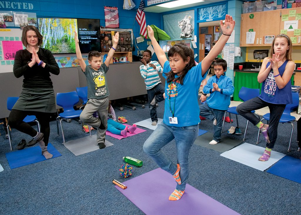 Photo: A student demonstrates the tree pose as teacher Stephanie Kennelly and classmates follow, using yoga mats inside of Kennelly's classroom.
