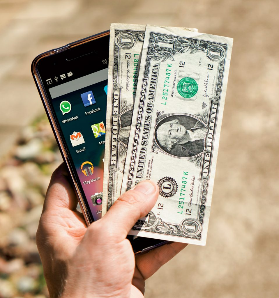 Photo: A hand holding money and a smartphone