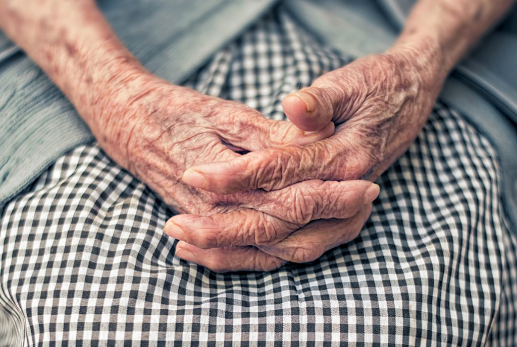 An elderly woman folds her hands in her lap.