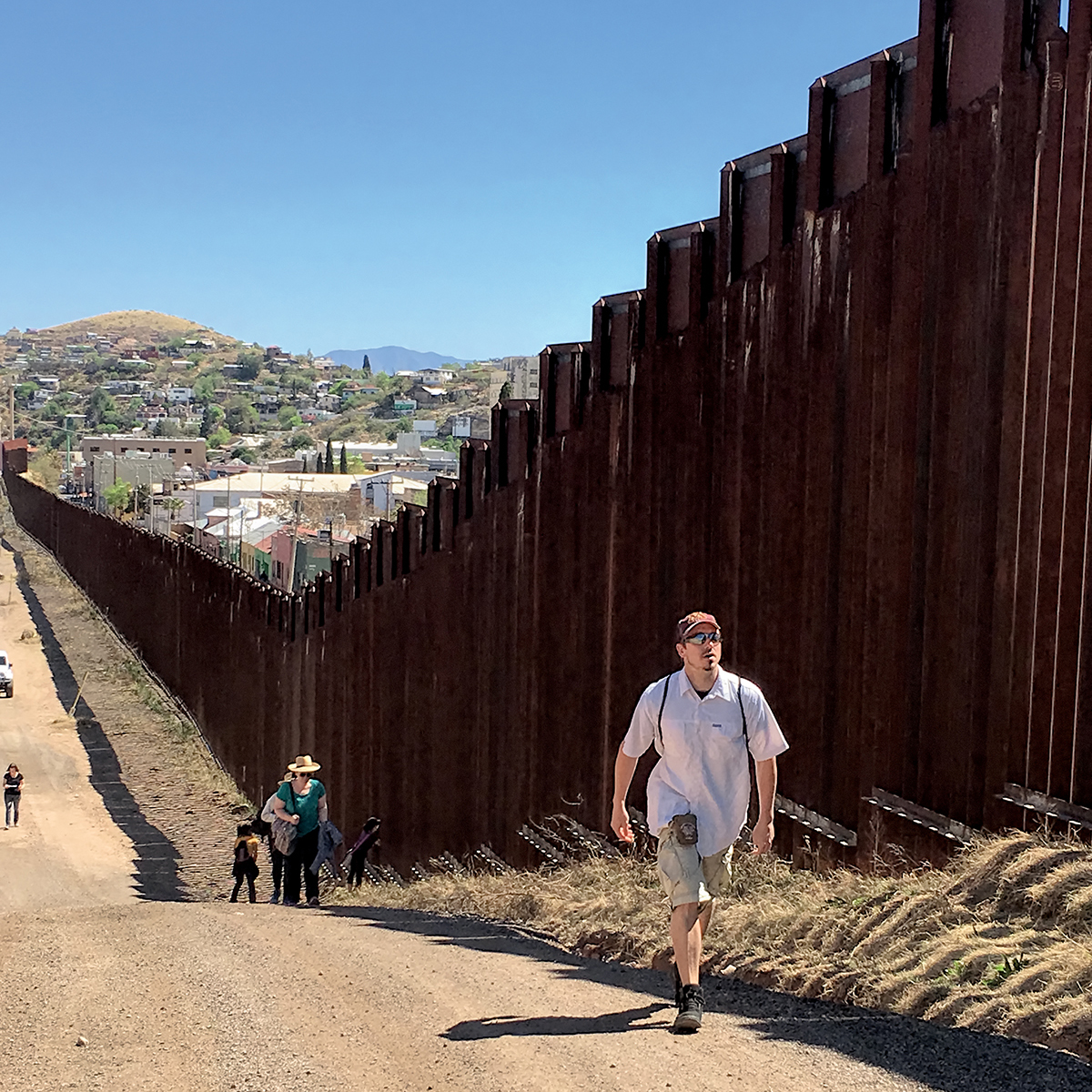 Students walk along the wall between Nogales, Arizona, and Nogales, Mexico.