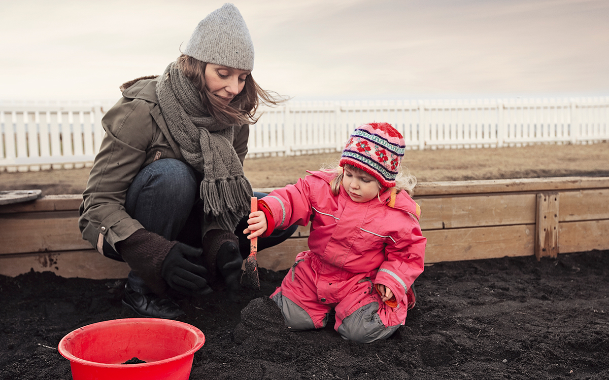 Mother and daughter playing in the sand