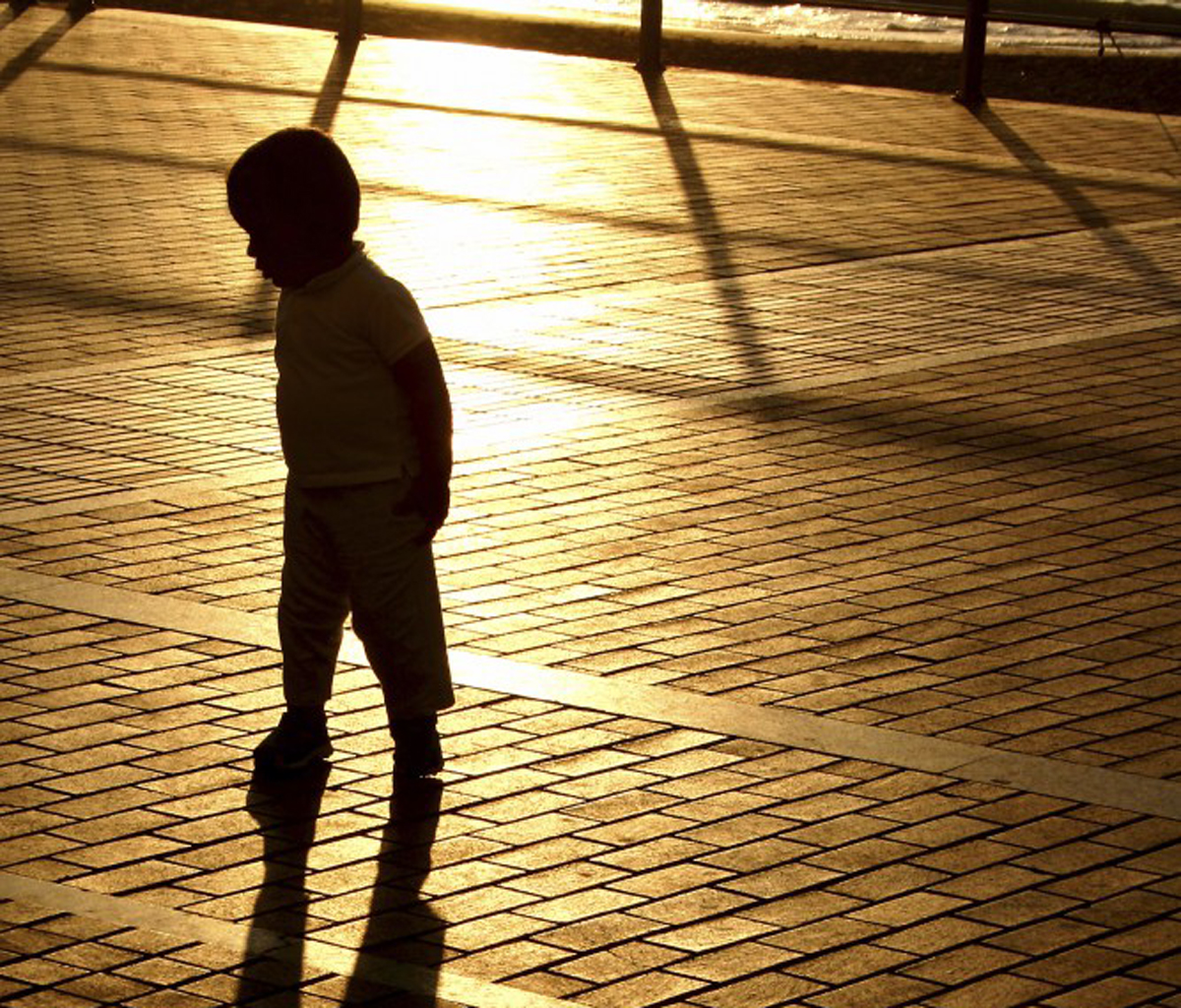 Color photo of a young child's silhouette, walking on brick pavement