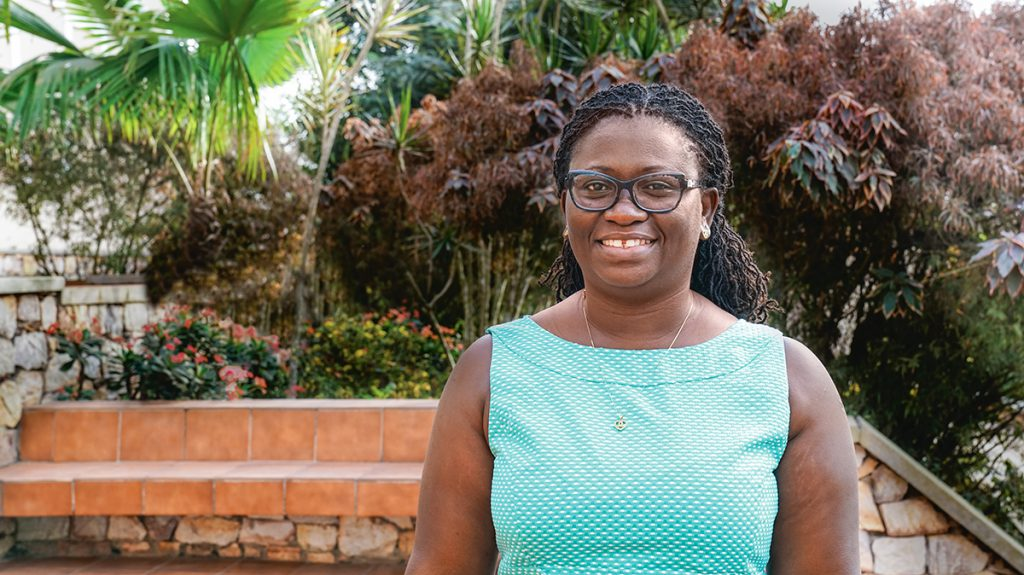 Millicent Adjei stands in front of a garden with a stone bench