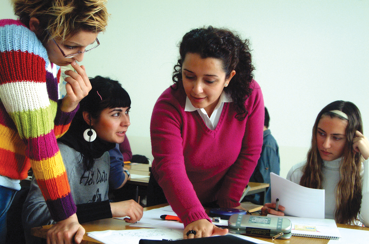 Teacher talking with three students