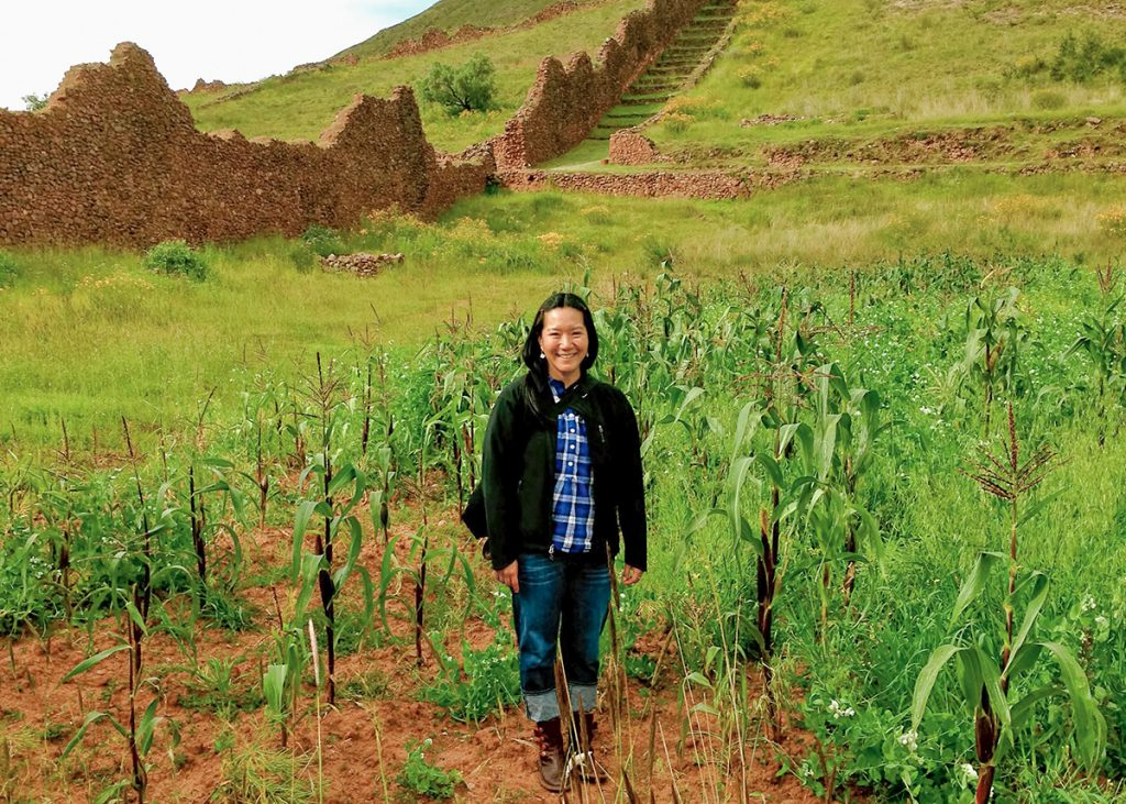 Photo of Elizabeth Sumida Huaman in a green field among ruins of tan stone walls