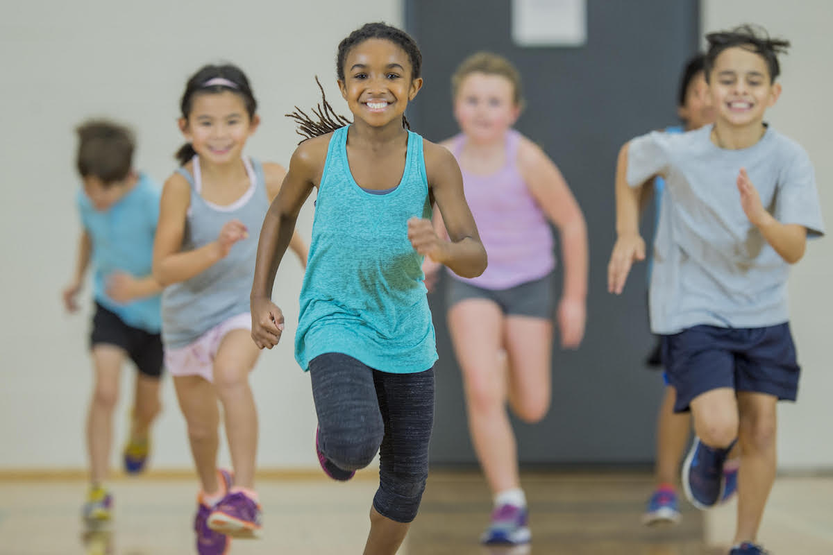 A multi-ethnic group of elementary school students are indoors in a school gym. They are wearing athletic clothing and shoes. They are jogging towards the camera.