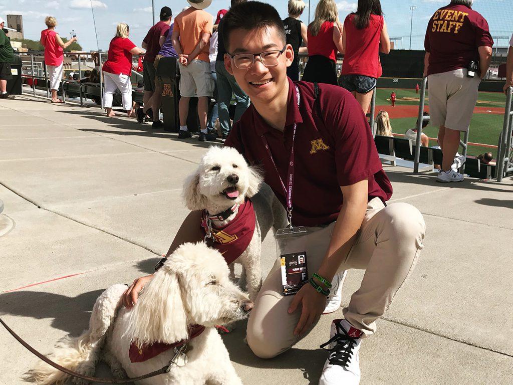 Yuran Wang at baseball field with dogs