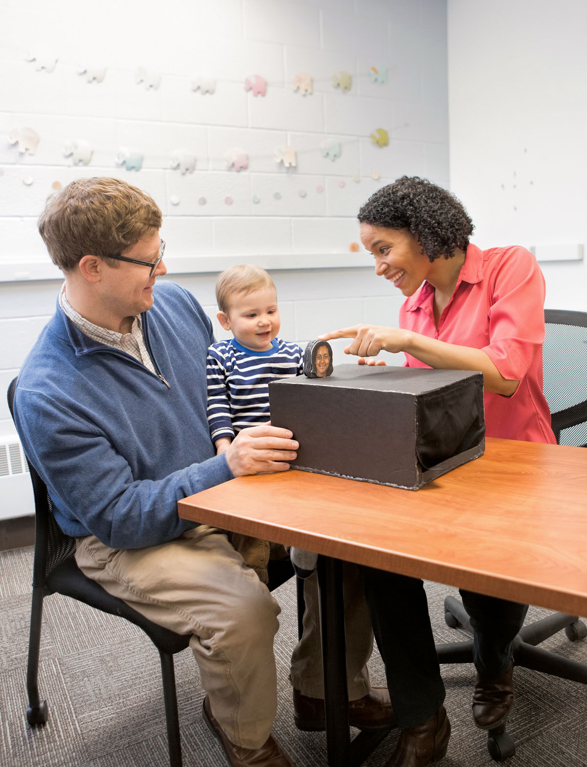 Photo of a father holding a baby engaged with a postdoctoral researcher conducting a study