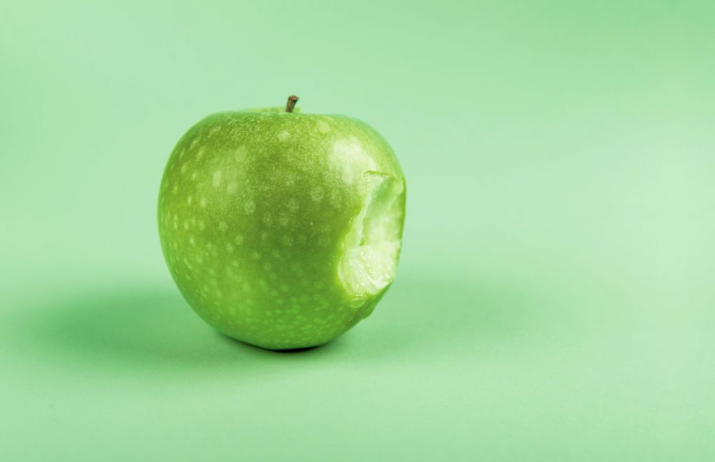 Photo of a Granny Smith (green) apple with a bite taken out of it.