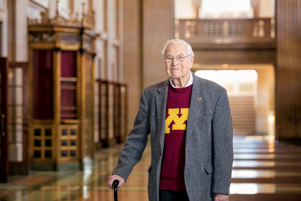 Neil Nickerson in the atrium of Northrop, maroon and gold sweatshirt under his jacket