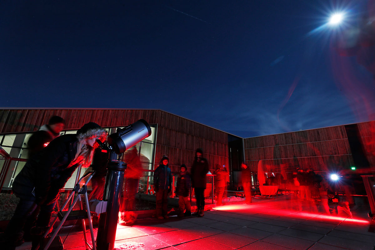Night photo of people on the infrared-lit observatory deck of the Bell Museum under the eclipsed moon.
