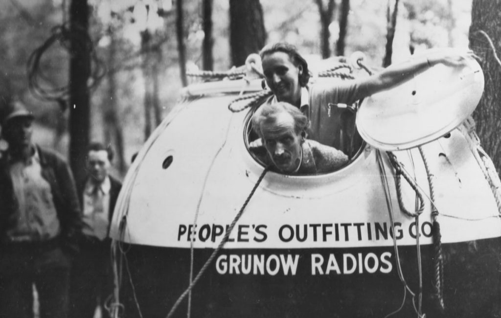 Jean and Jeannette Piccard opening the hatch of a pressurized 7-foot sphere in a wooded landscape
