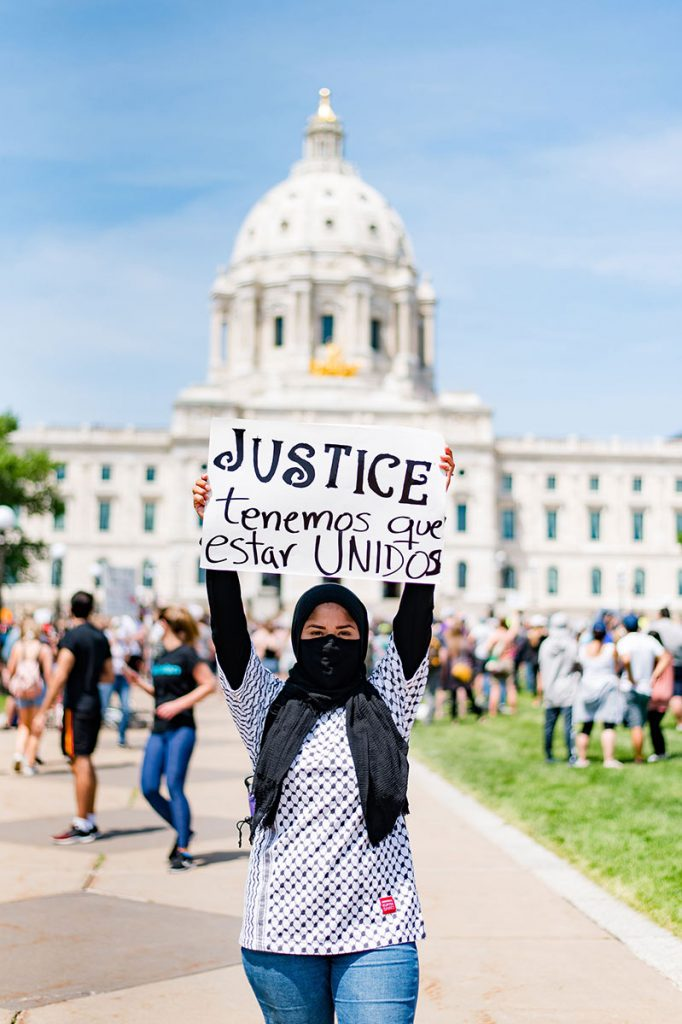 "Woman holding sign with the word ""justice"" while standing in front of the Minnesota State Capitol"