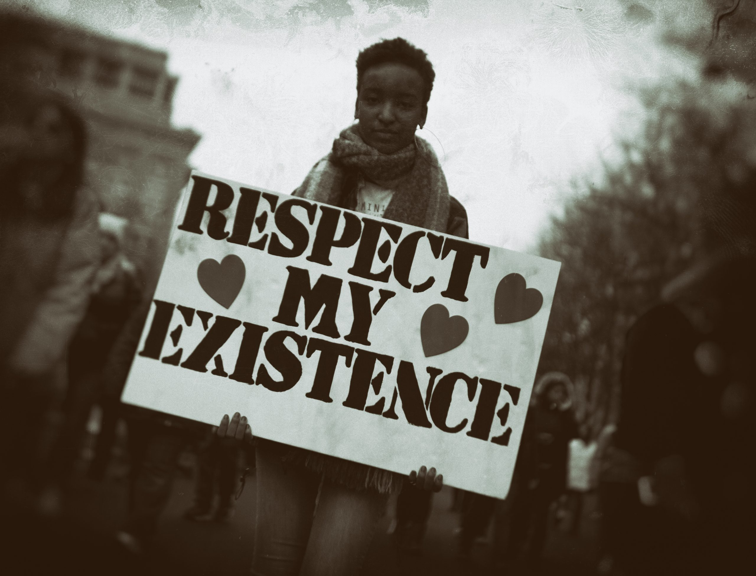 A person holding a respect my existence sign