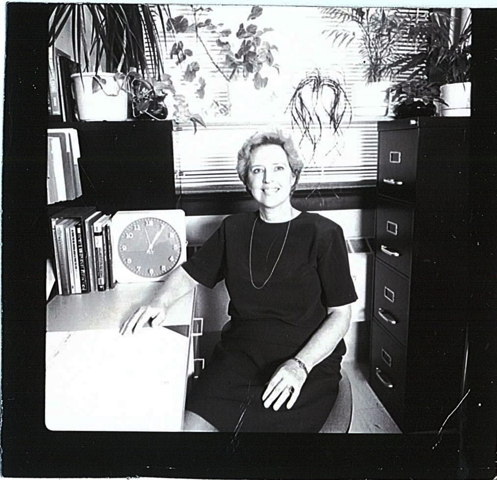 Kathy Rettig sitting at her desk