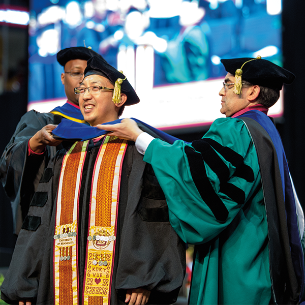 Michael C. Rodriguez helping a student with his regalia