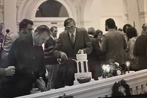 Dean William Gardner cutting a cake