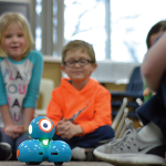 A group of children looking at a toy